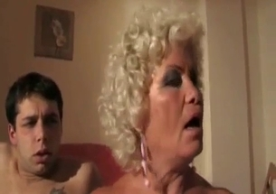 Old woman is blowing two cocks of her sons